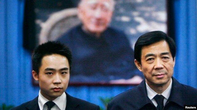 China's former Chongqing Municipality Communist Party Secretary Bo Xilai (R) and his son Bo Guagua stand in front of a picture of his father Bo Yibo, former vice-chairman of the Central Advisory Commission of the Communist Party of China. (File photo)