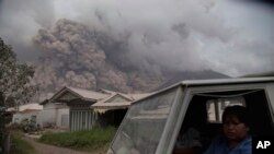 Residents ride in a truck as Mount Sinabung releases pyroclastic flows during its eruption in Karo, North Sumatra, Indonesia, Aug. 2, 2017.