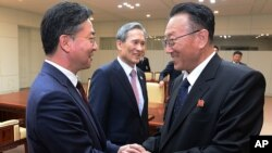 FILE - North Korea's Kim Yang Gon, right, speaks with South Korean Unification Minister Hong Yong-pyo, left, after their meeting at the border village of Panmunjom in Paju, South Korea, Aug. 25, 2015.