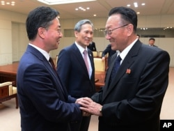 FILE - South Korean Unification Minister Hong Yong-pyo, left, shakes hands with Kim Yang Gon, a senior North Korean official responsible for South Korean affairs, after their meeting at Panmunjom. Yang Gon recently died in a car crash.