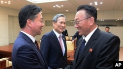 In this photo provided by the South Korean Unification Ministry, Unification Minister Hong Yong-pyo, left, shakes hands with Kim Yang Gon, a senior North Korean official responsible for South Korean affairs, after their meeting at Panmunjom, Aug. 25, 2015.