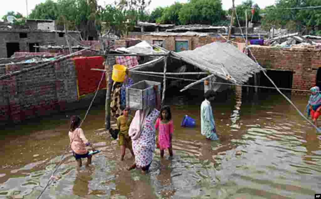 People move their belongings after their houses become flooded, September 16, 2011, in Hyderabad, Pakistan. (AP)