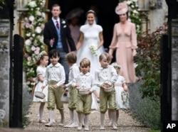 FILE - Prince George, il centro in primo piano britannico, reagisce dopo il matrimonio di sua zia, Pippa Middleton con James Matthews, nella chiesa di San Marco a Englefield, in Inghilterra, a maggio 20, 2017.