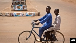 Two boys riding a bicycle pass by campaign posters for opposition candidate Gen. Muhammadu Buhari on a roundabout in Daura, his home town, in Katsina state in northern Nigeria, March 27, 2015.