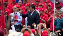FILE - Venezuela's President Nicolas Maduro speaks to workers of the state-run oil company during a demonstration outside Miraflores Presidential Palace in Caracas, Venezuela, June 22, 2016.