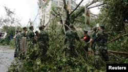 Paramilitary policemen remove toppled trees after Typhoon Meranti swept through Xiamen, Fujian province, China, September 15, 2016.