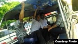 Dua wartawan Myanmar diangkut mobil polisi di Yangon.