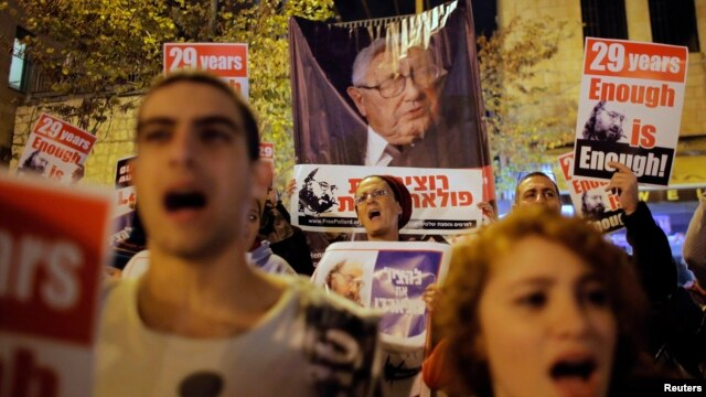 FILE - People shout slogans as in front of a placard depicting former U.S Secretary of State Henry Kissinger (C), during a protest calling for the release of Jonathan Pollard from a U.S. prison, outside U.S. Secretary of State John Kerry's hotel in Jerusalem, January 2, 2014.