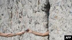 Jedan posetilac dodaje foto-aparat drugom kroz rupu u jednom od preostalih delova berlinskog zida