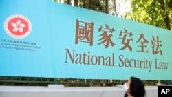 资料照:一名妇女走过香港街头宣传港版国安法的广告牌。(2020年6月30日)