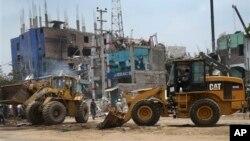 Para pekerja menggunakan bulldozer dan traktor untuk membersihkan reruntuhan gedung pabrik garmen di Savar, dekat Dhaka, Bangladesh (29/4).