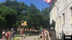 资料照片:游人与哈佛大学的约翰·哈佛铜像合影。