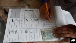 Seorang petugas pemungutan suara menyiapkan kertas suara untuk seorang pemilih yang akan melaksanakan hak pilih di tempat pemungutan suara untuk pilkada provinsi di Jamrud, distrik Khyber, Pakistan, Sabtu, 20 Juli 2019.