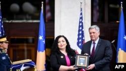 科索沃總統維約薩·奧斯馬尼(中)在頒獎典禮上將勳章交給美國大使菲利普·克斯內特。