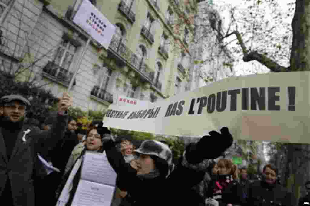 Demonstrators gather in front of the Russian embassy in Paris, Thursday, Dec. 8, 2011, to protest against Russian Prime Minister Vladimir Putin and his party, which won the largest share of a parliamentary election that observers said was rigged. Poster r