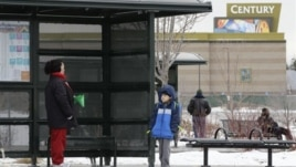 A woman and her grandson wait for a bus, near the fenced-in Century movie theater, the site of the deadly 2012 shootings, in Aurora, Colorado, January 15, 2013.