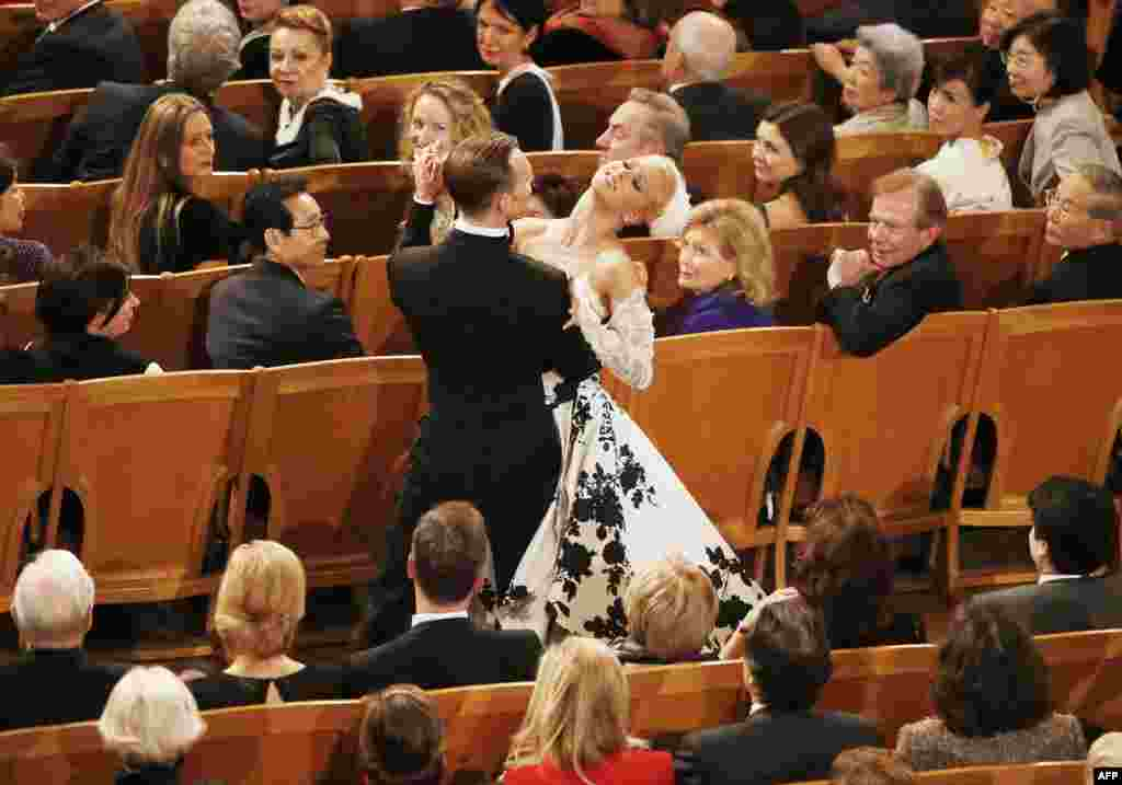 "A couple dances in the ""Golden Hall"" as Israeli Argentine-born conductor Daniel Barenboim conducts the Vienna Philharmonic Orchestra during the New Year's Concert in Vienna."