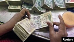 An employee counts Indian currency notes at a cash counter inside a bank in Kolkata, June 18, 2012.