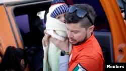 Un funcionario del gobierno de Ciudad Juárez sostiene al hijo de un peticionario de asilo mexicano, que con su familia acampaban cerca del cruce fronterizo de Paso del Norte, mientras esperaban para solicitar asilo en EEUU, porque se les mudará a un refugio local. Reuters.