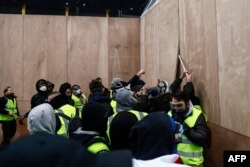 Protesters wearing yellow vests remove wooden boards protecting a shop windows during a demonstration against the rising costs of living that they blame on high taxes in Paris, Dec. 8, 2018.