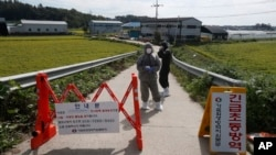 "Quarantine officials wear protective gear as a precaution against African swine fever at a pig farm in Paju, South Korea, Sept. 17, 2019. The notice reads: ""Under quarantine."""