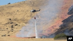 A California Highway Patrol helicopter drops water on a fire caused by the crash of a U.S. Air Force U-2 spy plane in the Sutter Butte Mountains near Yuba City, California, Sept. 20, 2016.