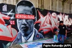 """Sebuah mural yang menggambarkan Presiden Indonesia Joko Widodo dengan pesan kesalahan jaringan """"404: tidak ditemukan"""" menutupi matanya, di Tangerang, Banten, sebelum dihapus dan polisi melakukan penyelidikan terkait hal tersebut. (Foto: AFP/Fajrin Rahardj"""