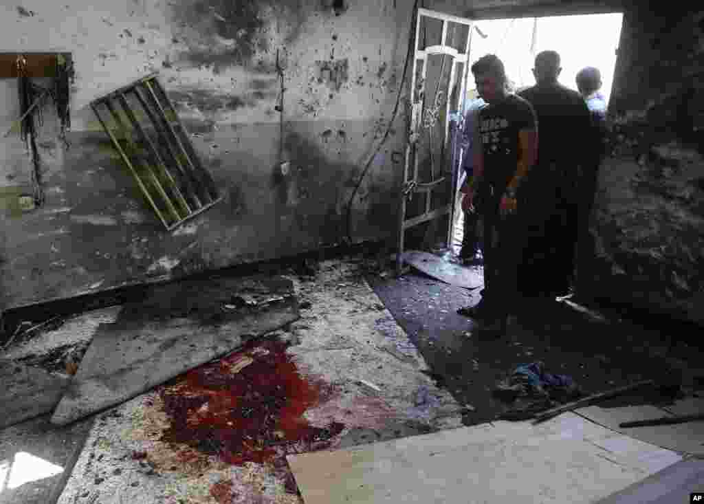 Worshipers view the damage to the inside of the Imam Ali mosque after a suicide bomb attack in New Baghdad, Aug. 25, 2014.