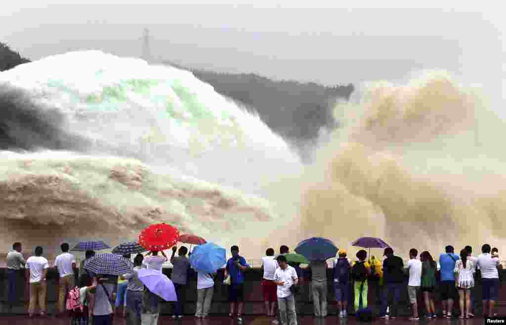 People watch as water gushes from the Xiaolangdi Reservoir section on the Yellow River, during a sand-washing operation in Jiyuan, Henan province, China, June 29, 2015.