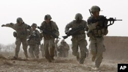 A US soldier returns fire as others run for cover during a firefight with insurgents in the Badula Qulp area, west of Lashkar Gah in Helmand province, southern Afghanistan, February 14, 2010