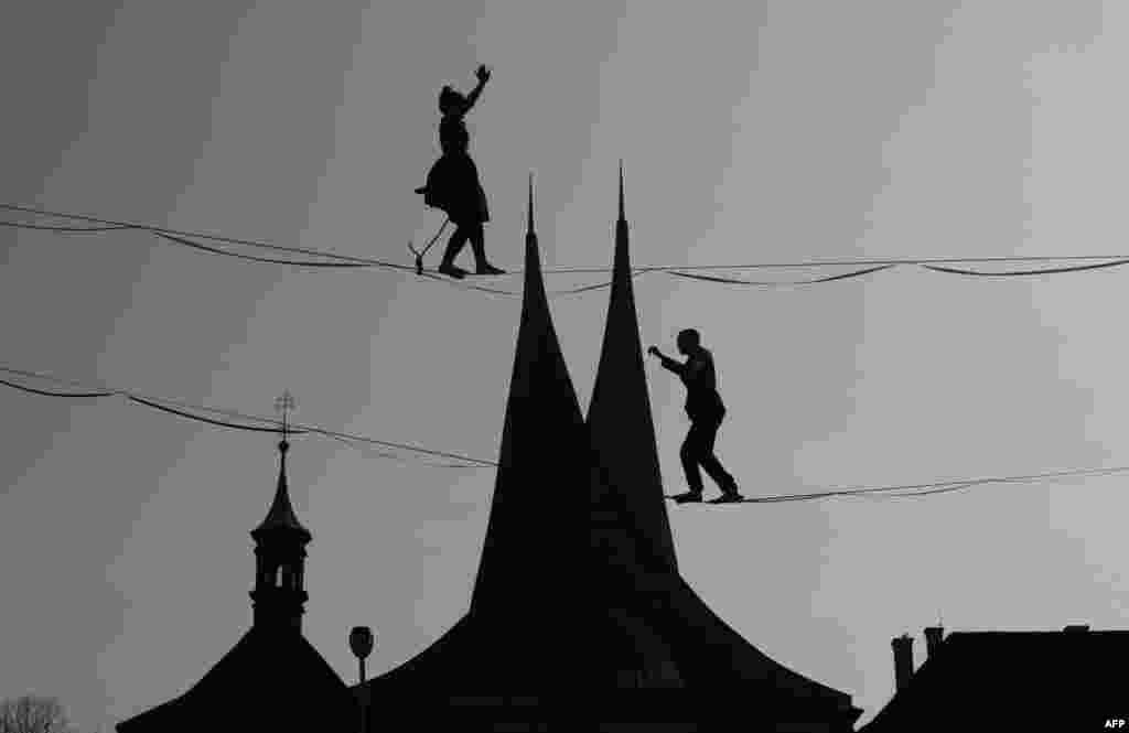 Tightrope artists balance on a rope in front of the Emmaus Monastery in Prague, Czech Republic.