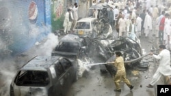 Firefighters spray water on damaged vehicles at the site of a car bomb blast in Quetta, Pakistan, Aug. 31, 2011