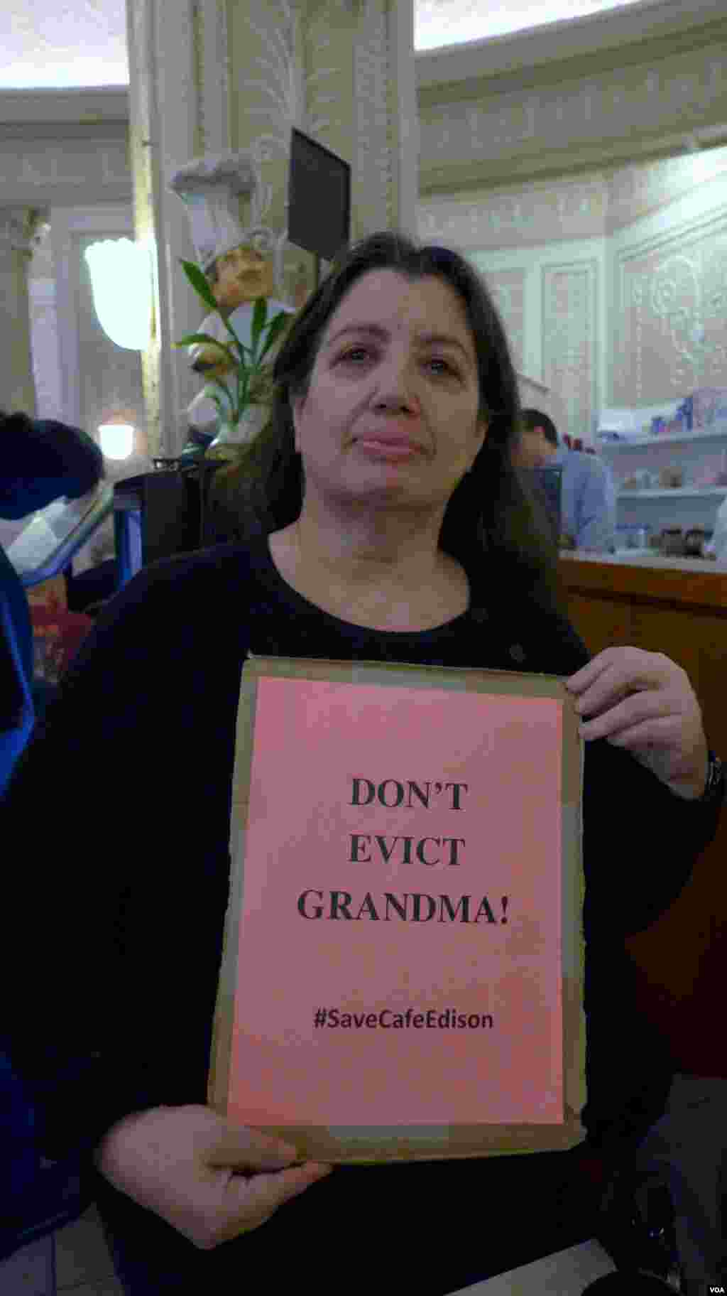 Barbara Nassberg shows off a poster protesting the move to close Café Edison, VOA / Jeff Lunden.