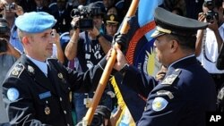 United Nations Police Pre-Deployment Training (UNPOL) officer Luis Carrilho (L) giving a flag to Longuinhos Monteiro (R) of the National Police of Timor-Leste (PNTL) during a ceremony in Dili, March 27, 2011