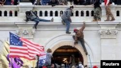 Una turba de simpatizantes del expresidente Donald Trump lucha contra policías en la puerta que rompieron al asaltar el Capitolio en Washington D.C. el 6 de enero de 2021.