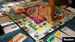 FILE - Players participate in a world record attempt by Monopoly enthusiasts across the world to set a Guinness world record for the largest simultaneous game of Monopoly, at a hotel in Madrid, Aug. 27, 2008.
