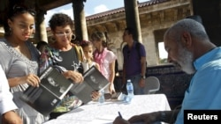 "FILE - Cuban author Leonardo Padura autographs his book ""The Faces of Padura"" in Havana, Oct. 31, 2015. Previously, Padura was awarded the 2015 Princess of Asturias award for literature."