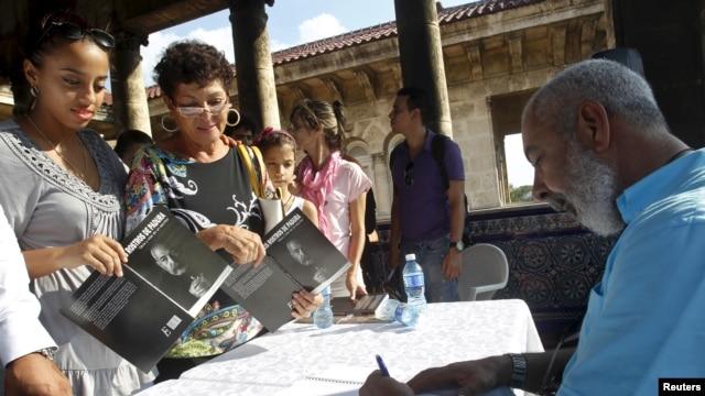 "FILE - Cuban author Leonardo Padura autographs his book ""The Faces of Padura"" in Havana, Oct. 31, 2015. Previously, Padura was awarded the 2015 Princess of Asturias award for literature."