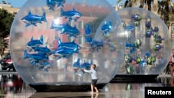 "A boy looks at fish-shaped balloons installed in a water fountain to mark April Fools' Day, called ""Poisson d'Avril"" in France, in the centre of Nice, April 1, 2015."