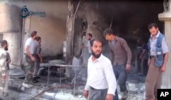 In this Oct. 1, 2015, image provided by the Syrian activist-based media group Qasioun News, Syrians use a fire extinguisher on the rubble of a building in the aftermath of a Russian airstrike, in Dair al-Asafeer, Syria.