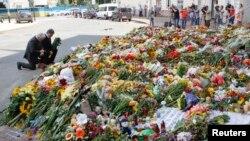 Presiden Ukraina Petro Poroshenko dan Duta Besar Belanda mengenang korban tewas pesawat Malaysia Airlines MH17 di luar Kedutaan Belanda di Kyiv (21/7).