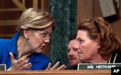 Sen. Elizabeth Warren, D-Mass., talks with Sen. Heidi Heitkamp, D-N.D., right, during a hearing on Capitol Hill in Washington, Jan. 30, 2018.