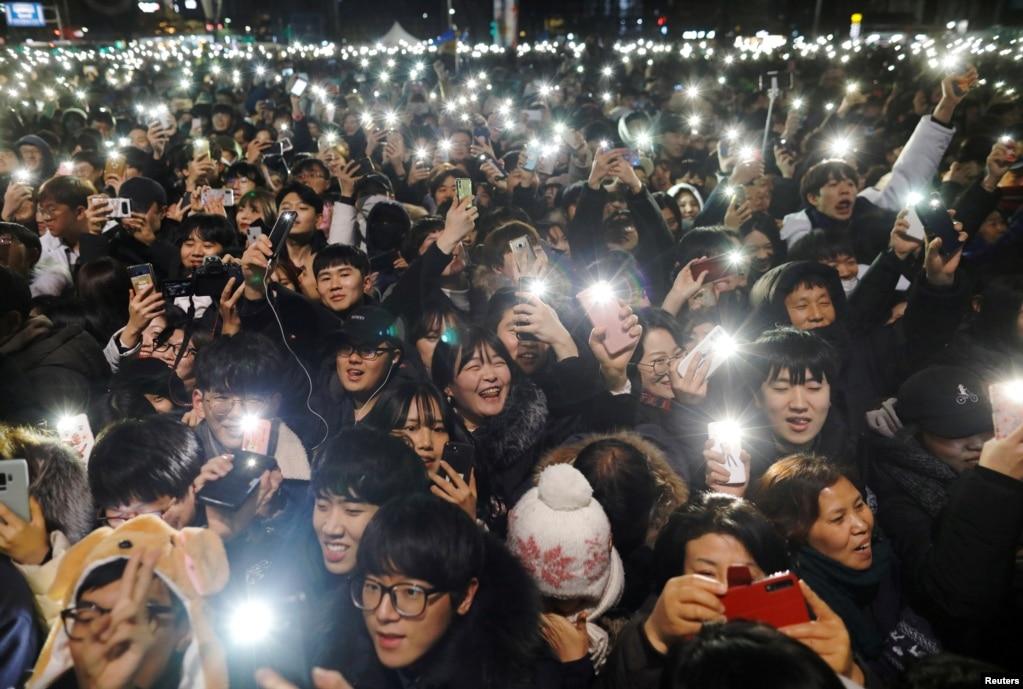 한국 서울에서 열린 신년행사에서 시민들이 휴대폰으로 불빛을 만들어내고 있다.