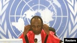 FILE - Judge Lloyd Williams of the International Criminal Tribunal for Rwanda adjusts his headphones, April 2, 2002, during one of the court's first sessions.