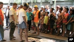 People look at bodies of flash floods victims in Davao city in southern Philippines June 29, 2011.