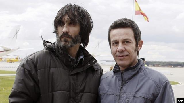 El Mundo correspondent Javier Espinosa (R) and freelance photographer Ricardo Garcia Vilanova arrive at the military airbase in Torrejon de Ardoz, near Madrid, March 30, 2014.
