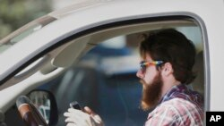FILE - An man works his phone as he drives through traffic in Dallas, Tuesday, Feb. 26, 2013. Texas lawmakers are considering a statewide ban on texting while driving. (AP Photo/LM Otero)
