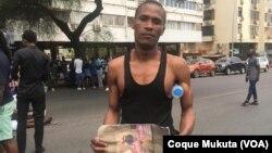 Cidadão mostra foto de vítima da violência policial