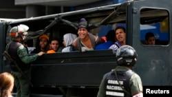 Estudiantes antigubernamentales gritan desde un camión luego de ser detenidos por la Guardia Nacional, tras una protesta en Caracas.