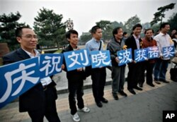 "Supporters of Liu Xiaobo hold cards that read ""We celebrate Liu Xiaobo winning the Nobel Prize"" outside a park in Beijing, China, 08 Oct. 2010"